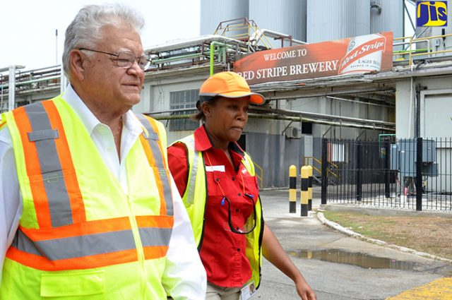 Industry, Commerce, Agriculture and Fisheries Minister, Hon. Karl Samuda (left) is being led on a tour of the Spanish Town Road-based Red Stripe plant by Local Raw Materials Business Development Manager, Dr. Cavell Francis-Rhiney discussing Cassava Farmers
