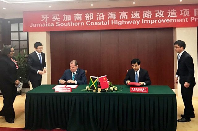 3 men sitting at a table signing contract for the highway improvement