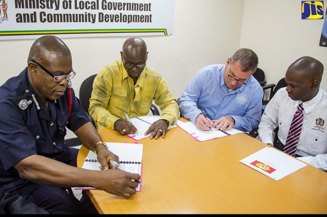 Desmond McKenzie signs contract for the purchase of two fire boats for the Jamaica Fire Brigade