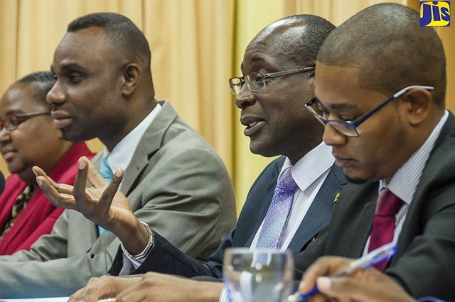 3 government officials sitting at a table give an update on developments in the education sector.