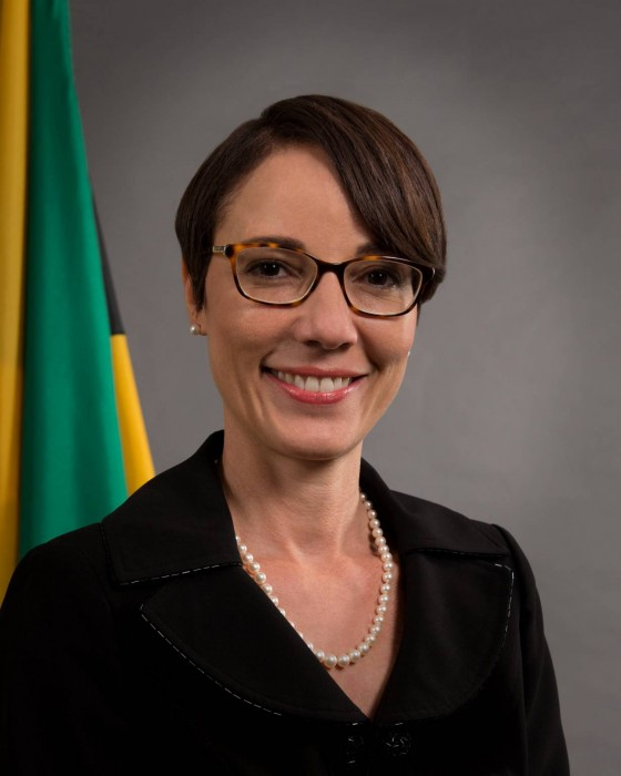 Foreign Affairs Senator Kamina Johnson Smith sitting in front of the Jamaican flag