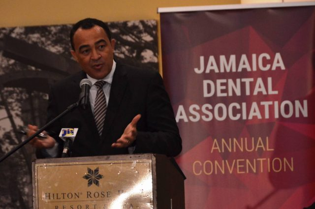 Minister of Health, Hon. Dr. Chris Tufton standing in front of podium disgussing dental sealent