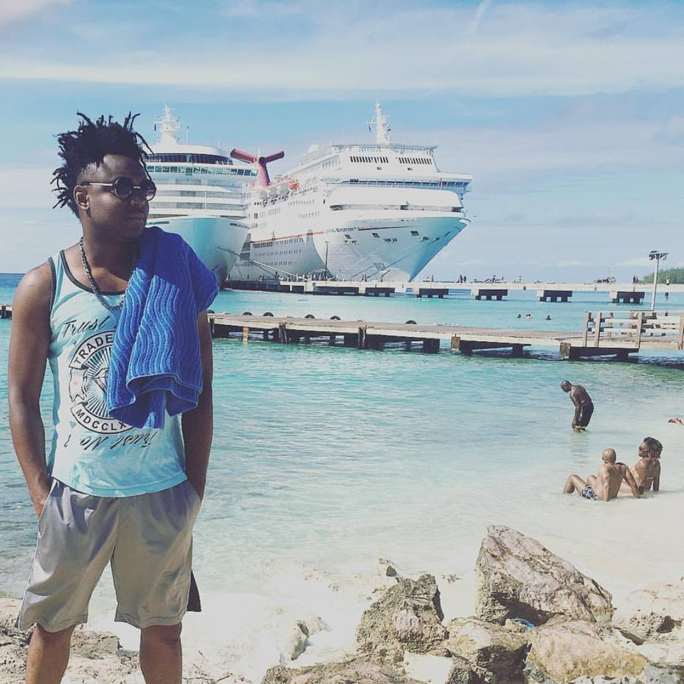 Artist Natel posing on a beach with a white ship in the background for womens violence