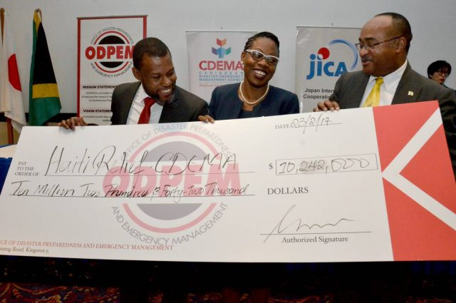 Executive Director of CDEMA Ronald Jackson hands over a cheque for a National Emergency Communication Network