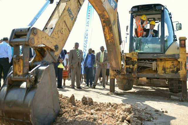 Prime Minister Holness gets assistance in operating a backhoe to address water needs