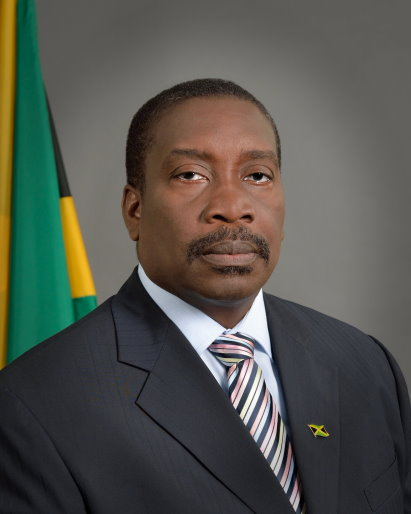 Robert Montague Minister of National Security sitting in front of the Jamaican flag