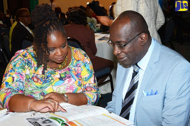 Minister of Education, Youth and Information, Senator the Hon. Ruel Reid (right), engages Director of the National College for Educational Leadership (NCEL), Rosemary Campbell-Stephens, at the start of a two-day International Conference organised by the College, at The Jamaica Pegasus hotel, in New Kingston,