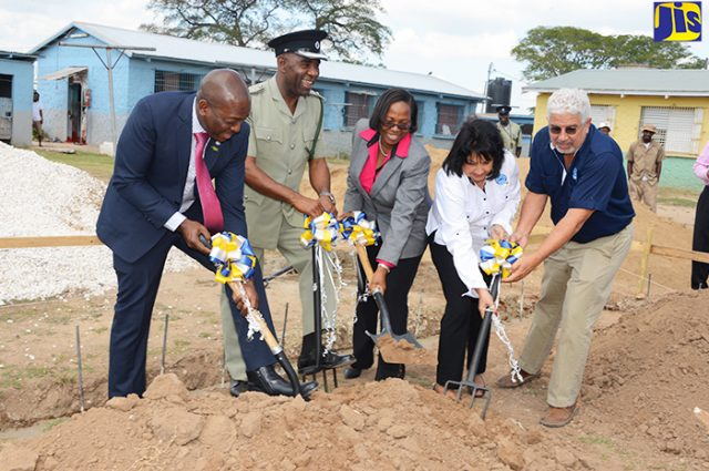 5 officials breaking ground with shovels for the construction of a new school at Tamarind Farm