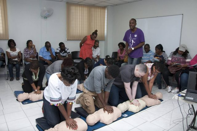 People doing chest compressions on dummies during CPR training