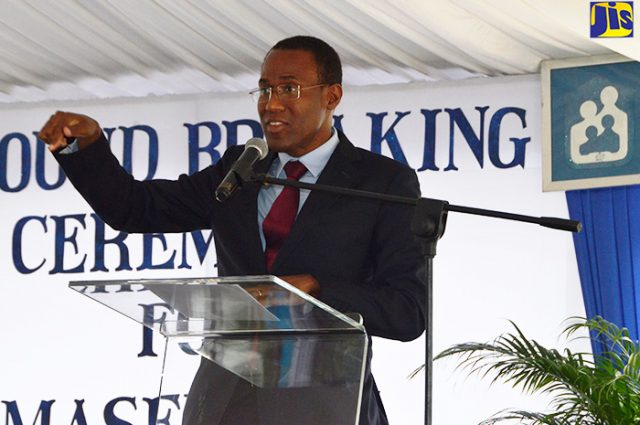 Chairman of the National Housing Trust (NHT), Ambassador Dr. Nigel Clarke speaking at a podium