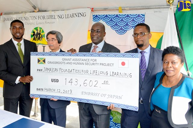 Ruel Reid and Japan's Ambassador to Jamaica Masanori Nakano display cheque
