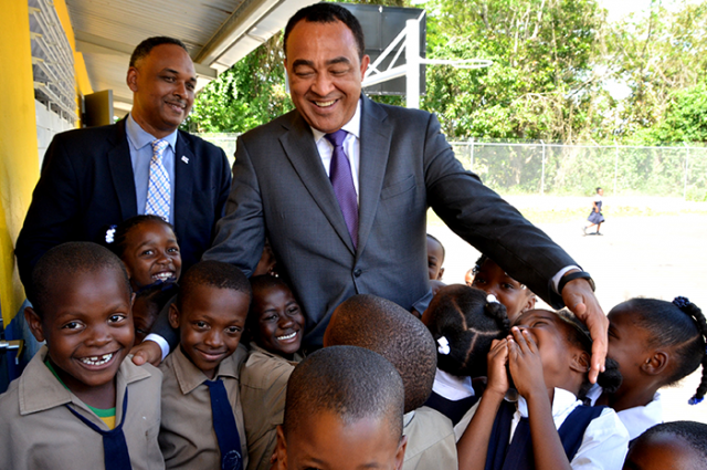 Christopher Tufton interacts with students of the Brown's Hall Primary School handing over expansion project