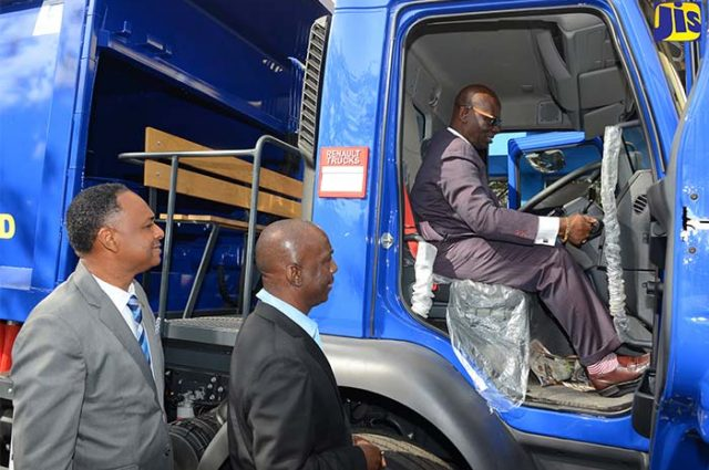 Desmond McKenzie, tries out the controls of one of the six new garbage trucks acquired for three of the NSWMA reginal offices