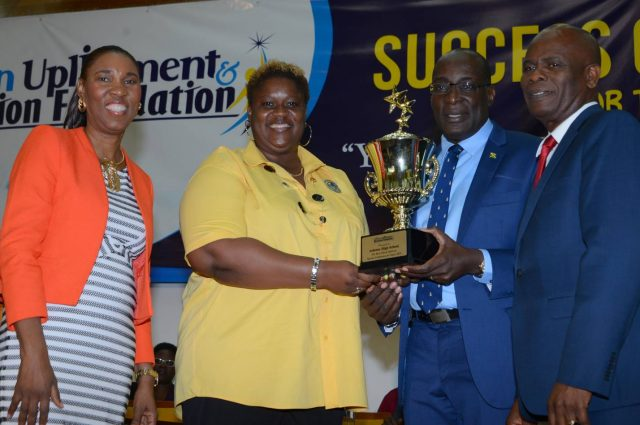 Ruel Reid (third left), presents a trophy to Personal Development Teacher at Ardenne High School, Kamika McKellop (second left), after the school emerged winner of last year's Best School Spirit and career choices