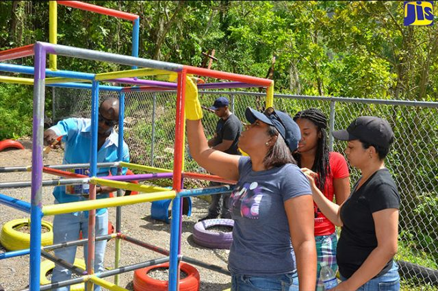 people repainting the playground at the basic school