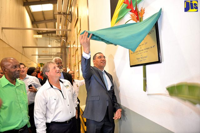 Andrew Holness unveils a plaque at the new production facility