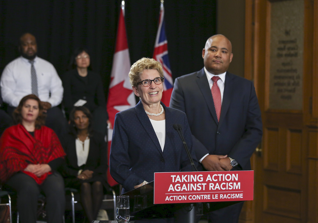Kathleen Wynne in front of microphone discussing the anti-racism doctorate legislation to Vision Newspaper Toronto